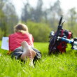 Stock Photo: Girl cyclist on halt reads on green grass outdoors in spring park