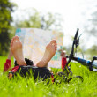 Stock Photo: Cyclist on halt reads map lying on green grass in spring park