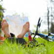 Cyclist reads a map lying barefoot on green grass outdoors in summer park — Stock Photo #24898039