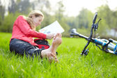 Girl cyclist on a halt reads lying in fresh green grass barefoot — Stock Photo