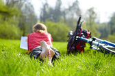 Girl cyclist on a halt reads on green grass outdoors in spring park — Foto Stock