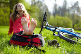 Happy girl cyclist enjoying relaxation sitting barefoot in spring park — Stock Photo