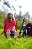 Happy girl biker enjoying relaxation sitting barefoot in green grass — Stock Photo