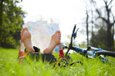 Cyclist reads a map lying barefoot on green grass outdoors in summer park — Stock Photo