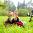 Stock Photo: Barefoot cyclist on halt reads lying in fresh green grass