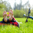 Cyclist on a halt reads lying in fresh green grass barefoot — Stock Photo