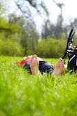 Barefoot tourist enjoying relaxation lying in fresh green grass — Stock Photo