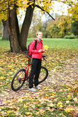 Young girl cyclist with bike enjoy vacation in autumn park — Stock Photo