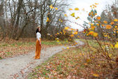 Young beautiful woman with flower wreath outdoors in the autumn park — ストック写真