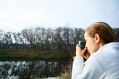 Woman hiker with thermo cup of tea in hand on the autumn nature — Stock Photo