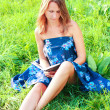 Young woman sitting in grass reading book — Stock Photo #6494719
