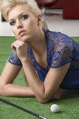 Sexy blondýnka platí golf ležící na trávě — Stock fotografie