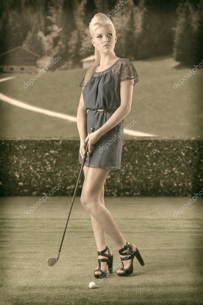 Beautiful blonde girl in full lenght plays golf with blue short dress and hig shoes, vintage color shot — Stock Photo #12492384