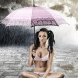 Sexy brunette with umbrella, sitting with crossed legs — ストック写真