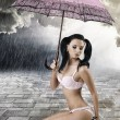Sexy brunette sitting with umbrella, touches her shoe — Foto de Stock