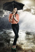 Beautiful woman with umbrella, takes tatch with both hands — Stock Photo