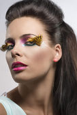 Girl with feathered makeup turned at right — Stock Photo