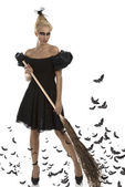 Sexy girl in halloween suit with besom in all hands — Stock Photo