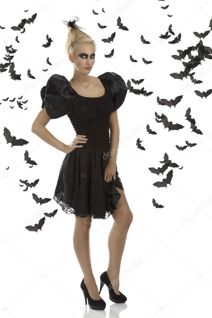 Pretty blonde girl with gothic dress and dark make-up, turned of three quarters at left and looks in to the lens — Stock Photo #13615408