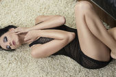 Sexy brunette lying on carpet on the her back — Stock Photo