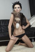 Sexy brunette with slip and fur collar touches her slip — Stock Photo