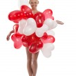 Blonde girl with many balloons on her body looks in to the lens — Stock Photo #13770421