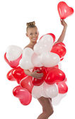 Blonde girl with many balloons on her body takes one balloon — Stock Photo