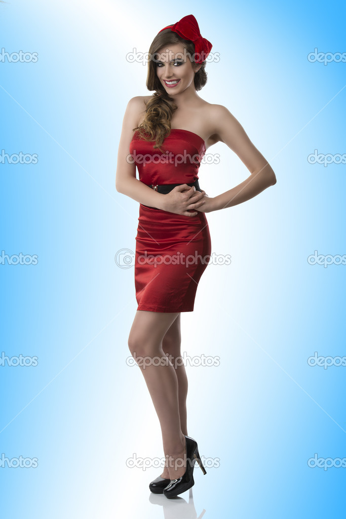 Beautiful girl with red and elegant dress and one bow in the hair, she looks in to the lens and laughs, her hands are both near the left hip  Stock Photo #13887484