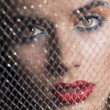 Close-up portrait of girl behind net — Stock Photo