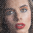 Portrait of girl behind net looks in to the lens — Stock Photo #14094458