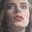 Royalty-Free Stock Photo: Portrait of girl behind net looks up