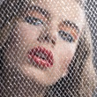Stock Photo: Portrait of girl behind net with bent head