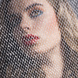 Stock Photo: Portrait of girl behind net turned at right