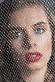 Portrait of girl behind net looks in to the lens — Stock Photo