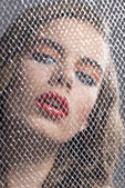 Portrait of girl behind net with bent head — Stock Photo