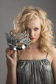 Blonde girl with silver mask in front of the camera — Stock Photo