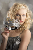 Blonde girl with silver mask turned of three quarters — Stock Photo