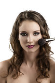 Girl getting made-up with brushes, she smiles — Stock Photo