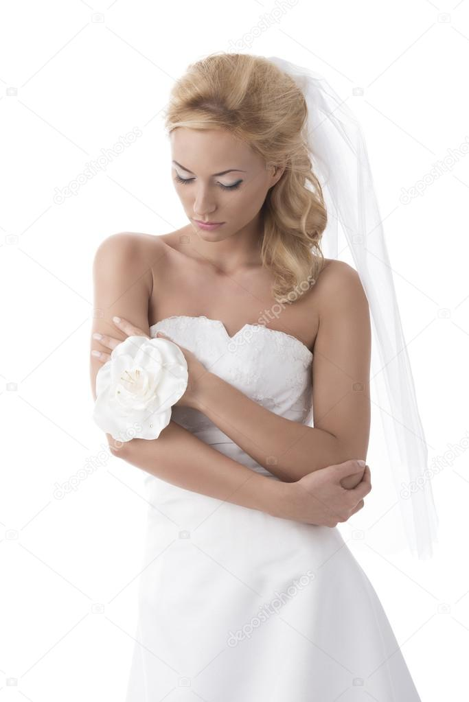 Beautiful blonde girl with white wedding dress, she looks down with right hand on the left elbow and the left hand on the right arm  Stock Photo #18970069