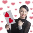 Pretty brunette with valentine postcard smiles — Stock Photo