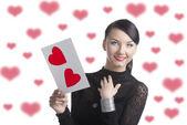 Pretty brunette with valentine postcard smiles — Stock Photo
