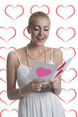 Blonde girl reads valentine postcard — Stock Photo