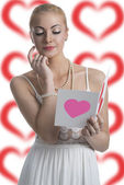 Blonde girl looks valentine postcard — Stock Photo