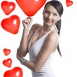 Sexy brunette takes the heart shaped balloon - Stock Photo