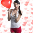 Royalty-Free Stock Photo: Sexy brunette with heart shaped balloon sends a kiss
