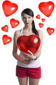 Sexy brunette with heart shaped balloon in front of the camera — Stock Photo