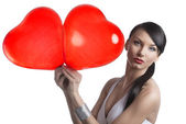 Sexy brunette takes two heart shaped balloons with both hands — Stock Photo