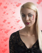 Sexy girl with heart shaped decoration looks in to the lens — Stock Photo