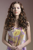 Pretty brunette with curly hair in front of the camera — Stock Photo