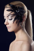 Girl with feathered accessory, she looks down — Stock Photo